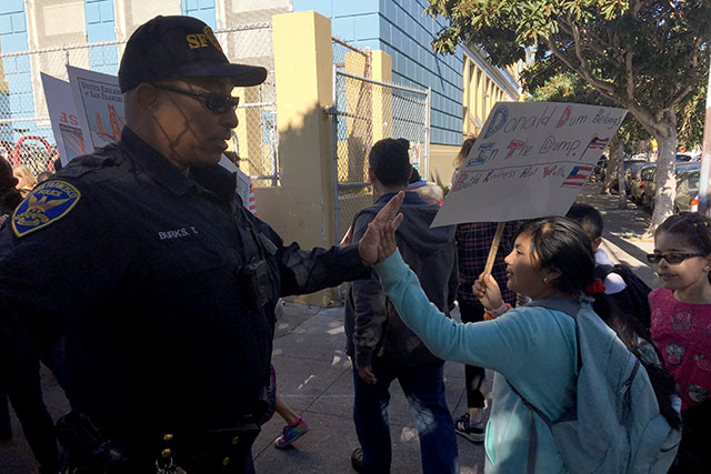 A police officer gives high-fives to students returning to Buena Vista Horace Mann school after a march around the Mission. Photo by Laura Wenus