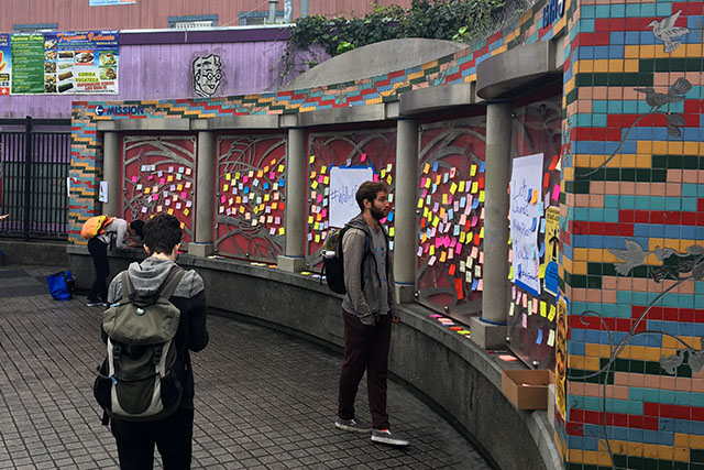 Commuters read notes left at the Wall of Empathy.