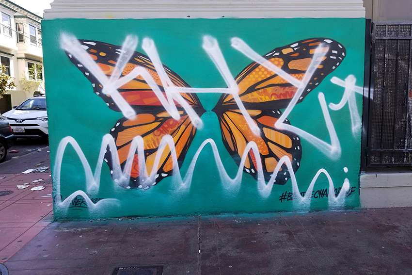 Butterfly wings mural defaced with 'KHY' tag, then covered up