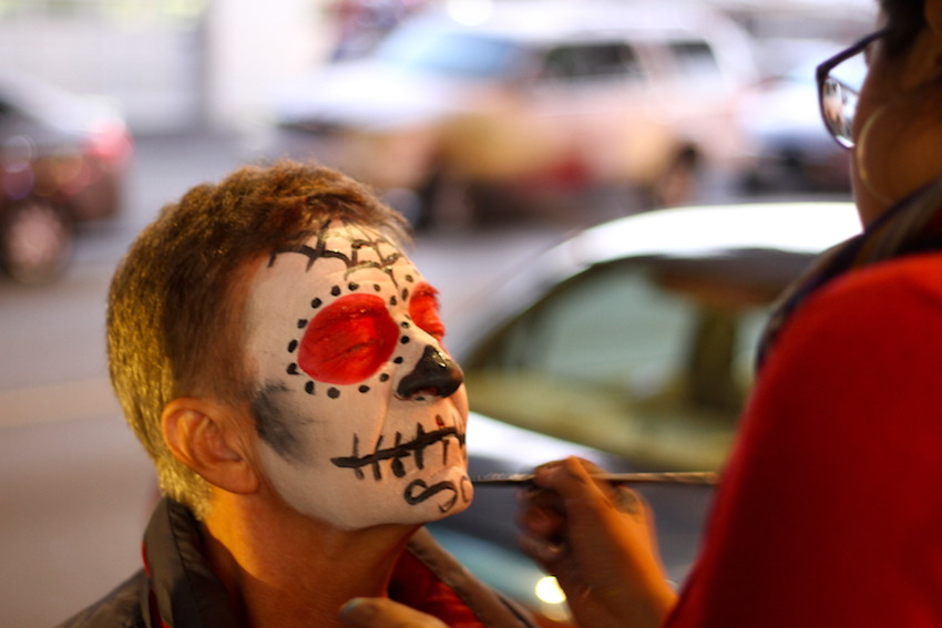 Sonia Hurtado of Fremont paints the face of Kurt Berggren, also of Fremont, on 24th Street Thursday. Hurtado and Berggren were surprised to learn they both lived in Fremont.