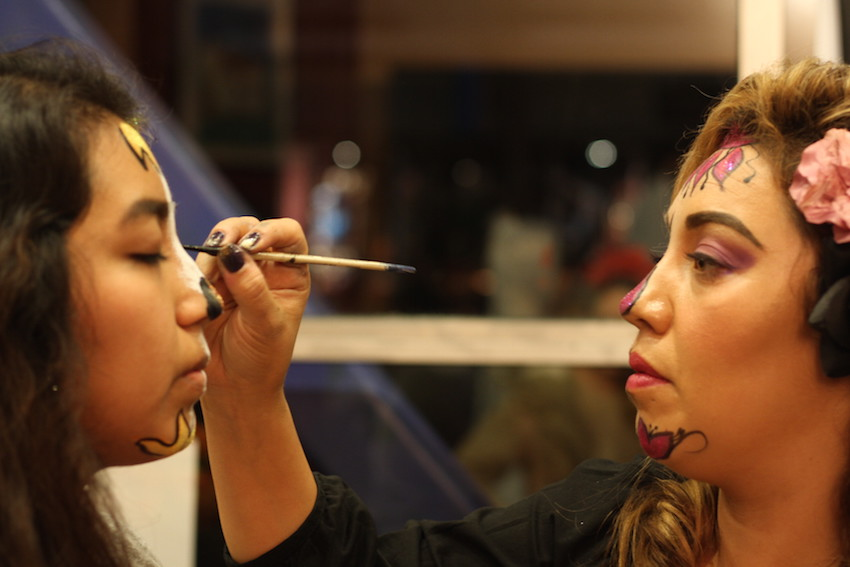 Inside the Mission Cultural Center, Jennnifer Coll paints the face of Lupe Velazquez.