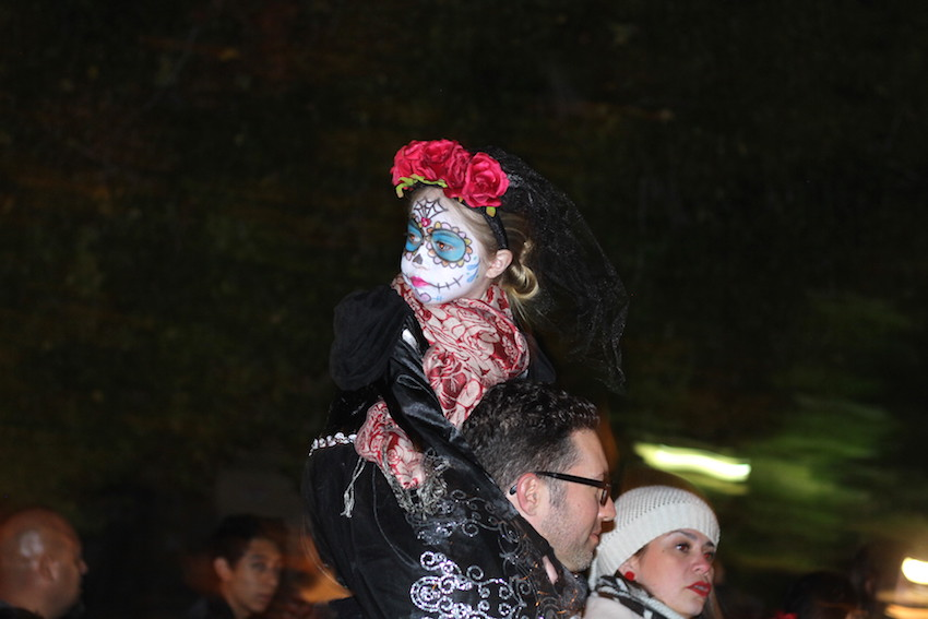 A young reveler gets a boost during the Dia de los Muertos procession.