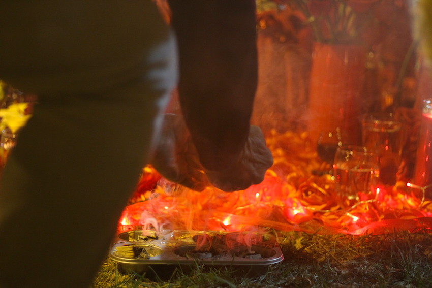 A man kneels to scoop up incense at an altar dedicated to Santa Muerte.