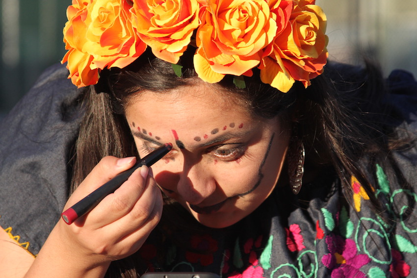 "Paulina Avila-Martinez of San Leandro applies make-up at the Dia de Los Muertos celebration at Garfield Square in San Francisco's Mission District Thursday Nov 2nd. Avila-Martinez is half-Mexican and half-Chilean, and grew up with the Day of the Dead. It's a ""reminder that life and death are both very important,"" she says. ""Nothing in this world lasts forever. We can't celebrate life without understanding death."""