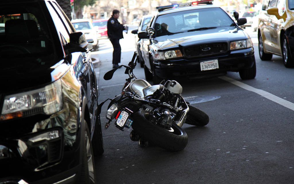 Car strikes motorcycle on Valencia, rider injured