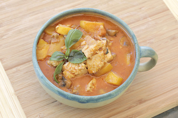 Massaman curry with a deep orange colored sauce with large chunks of tofu and potato with a quad basil leaf garnish, in a blue and light green ceramic bowl with a single handle on a wooden cutting board.