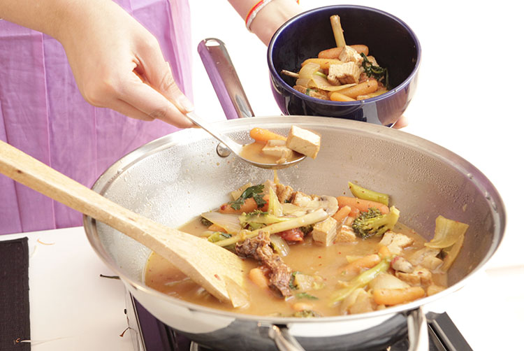 Student wearing a lavendar apron, spooning completed Tom Yam soup recipe made with fresh chili paste from stainless steel wok into a dark blue ceramic bowl using a stainless steel spoon. A large wooden spoon rests in the wok with large piecs of broccoli, onion, tofu and soup broth.