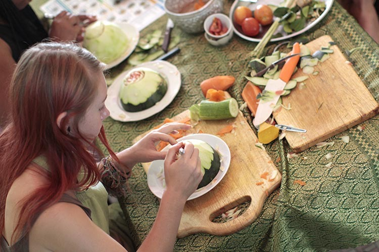 Student carving half of watermelon flower with traditional ornate carving knife. On the table sits other watermelon halves, carrots, cucumbers, cutting boards and various sized carving knives.