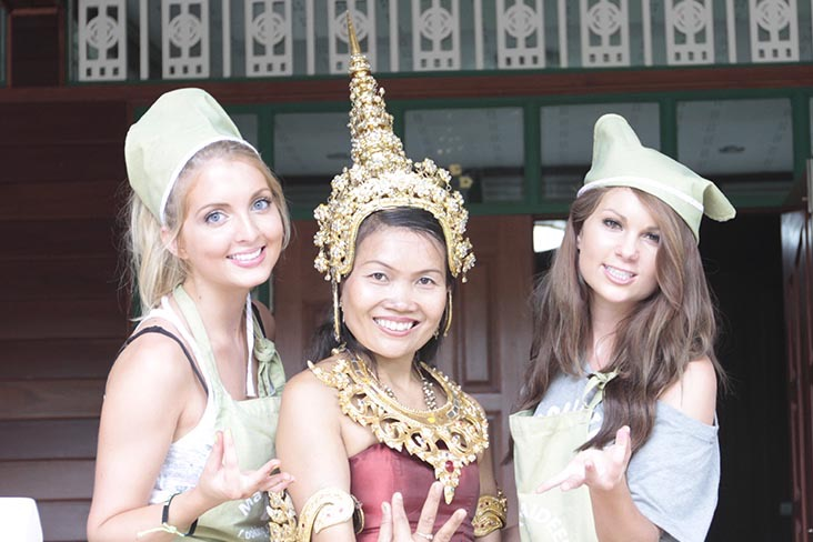 Group of students posing with traditional Thai dance hand gestures.