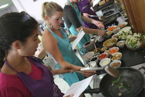 Group of students cooking with woks.