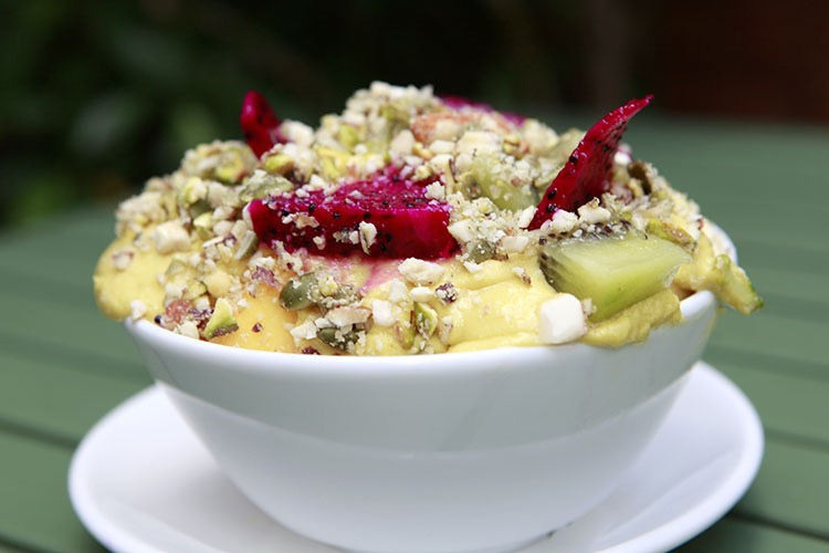 Fruit salad with mango sauce and chopped pistachios.