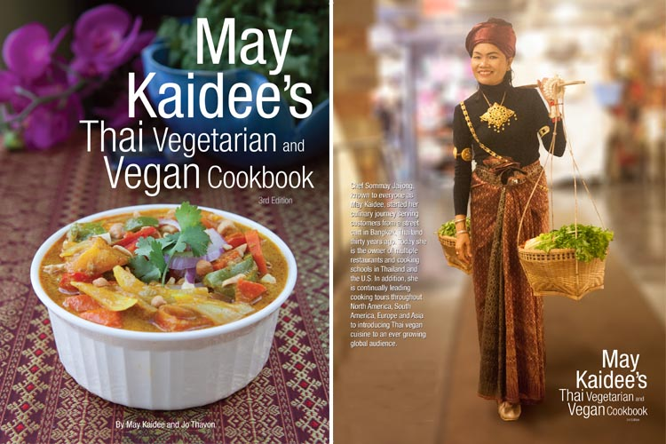 The front and back covers of the third edition May Kaidee Thai Vegetarian and Vegan Cookbook. The cookbook cover photo shows massaman curry in a white ceramic dish. The back cover shows the company founder May Kaidee wearing traditional Thai dress and holding traditional bamboo Thai baskets with vegan ingredients, attached to a bamboo stick balanced her shoulder.