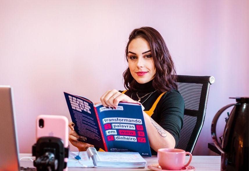 influenciadores digitais: imagem de uma mulher sentada em uma cadeira folheando uma revista com um celular gravando a imagem
