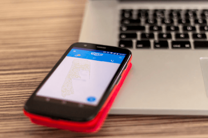 principais redes sociais: imagem de um celular apoiado em um notebook com a tela do skype aberta