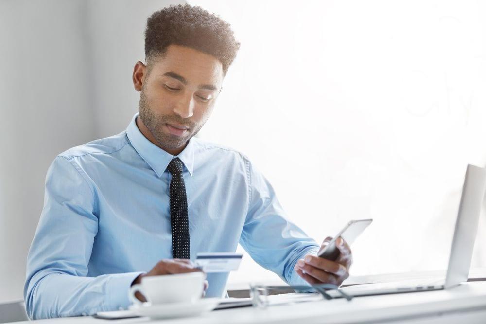 pagamento pelo whatsapp - foto homem usando celular para pagamento
