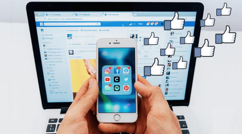 Curtidas no Facebook: imagem de uma mão segurando um celular com vários emolis de likes.