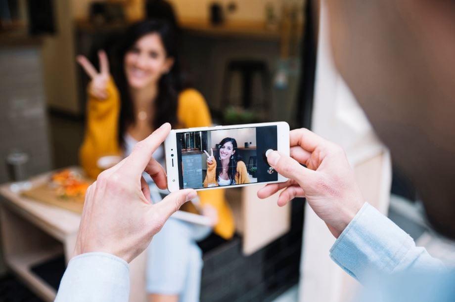 Foto de perfil do Instagram: imagem de uma mulher fazendo pose para foto e outra pessoa fotografando pelo celular.