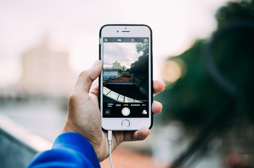 Time Lapse no Instagram: imagem de uma mão segurando o celular com a câmera aberta para tirar foto.