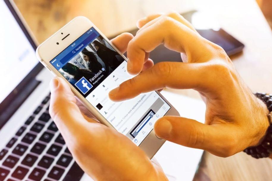 Alcance orgânico no Facebook: imagem de uma pessoa mexendo no Facebook pelo celular