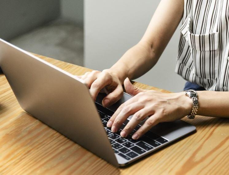 Marketing de Conteúdo: imagem das mãos de uma mulher digitando no notebook apoiado em cima da mesa.
