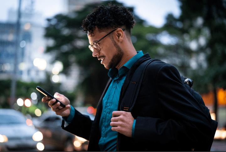 Imagem de um homem olhando para a tela do seu celular. Ilustra o post sobre como criar link para whatsapp