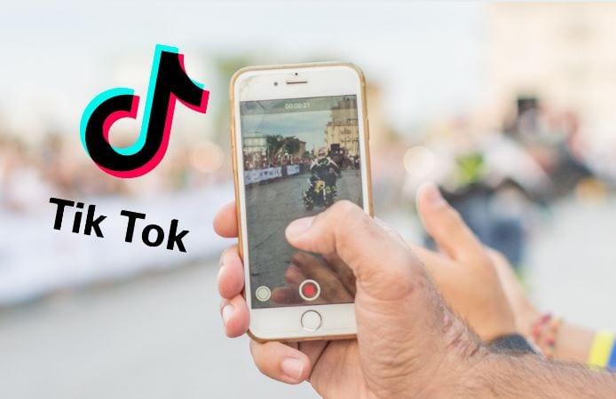Como fazer vídeo no Tik Tok: imagem de uma mão gravando um vídeo no celular com o logo ao aplicativo Tik Tok