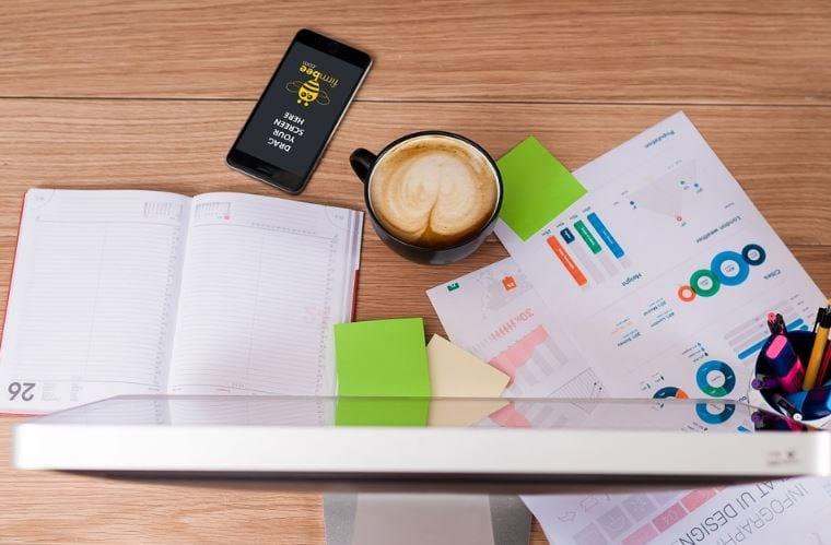 Campanha de Marketing: imagem de uma mesa com anotações em papéis (gráficos, contas) uma xícara de café e um computador.