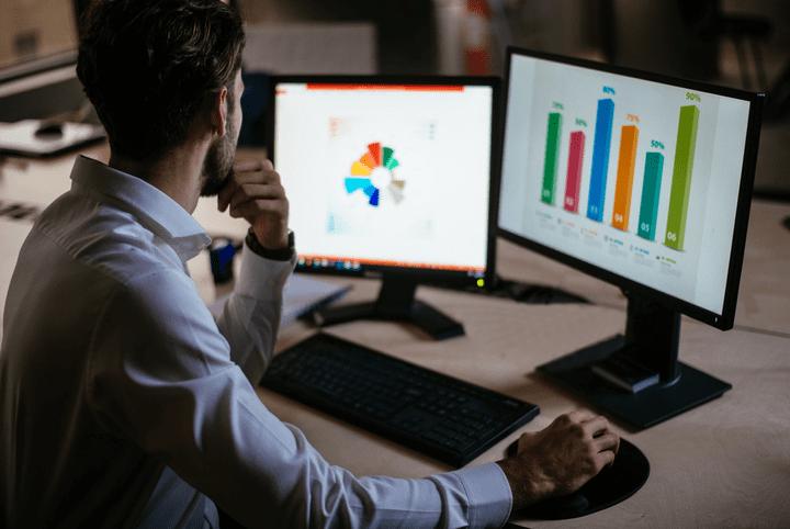 social analytics: imagem com uma pessoa analisando dados e gráficos em dois computadores