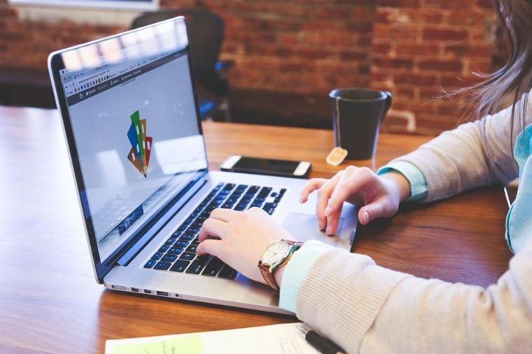 Como fazer um infográfico: imagem das mãos de uma mulher mexendo no computador