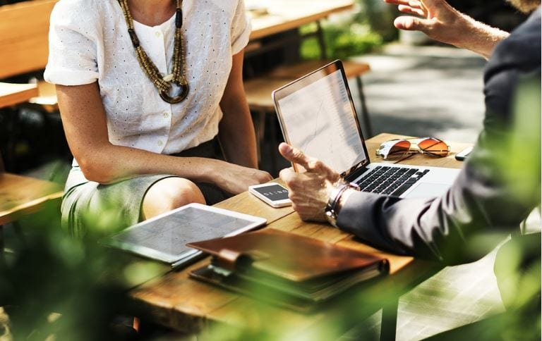 B2B Marketing: imagem de duas pessoas pessoas vestidas com roupa de trabalho conversando com um notebook na mesa.