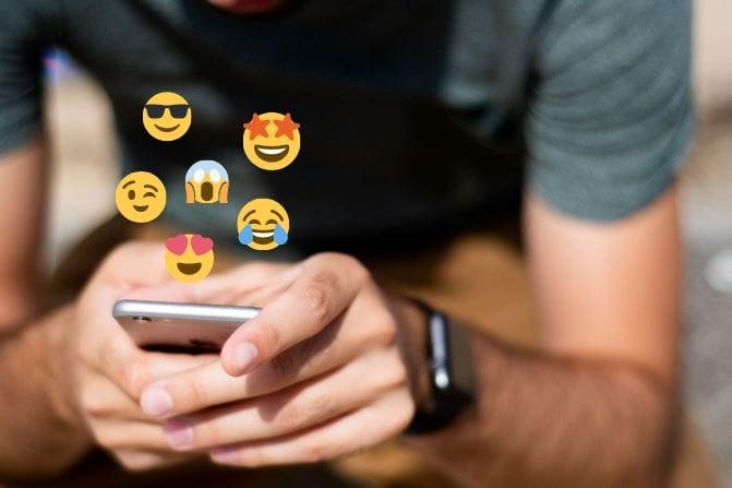 Emoticons para Instagram: imagem de duas mãos segurando um celular com emojis saindo da tela.