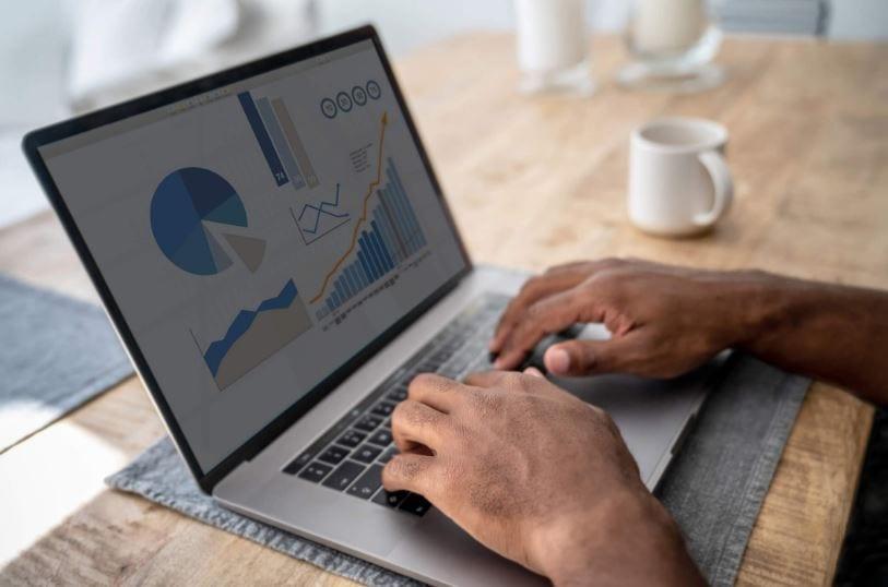 Como criar conta no Google Analytics: imagem das mãos de um homem digitando em um notebook apoiado em uma mesa de madeira com uma caneca de café ao lado.