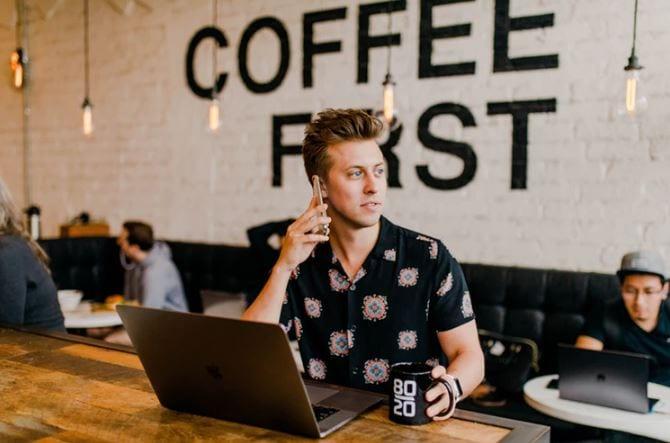 Social Media Manager: Um homem jovem, em uma cafeteria, segurando com o celular no ouvido, com o notebook aberto na mesa ao lado de uma caneca de café.