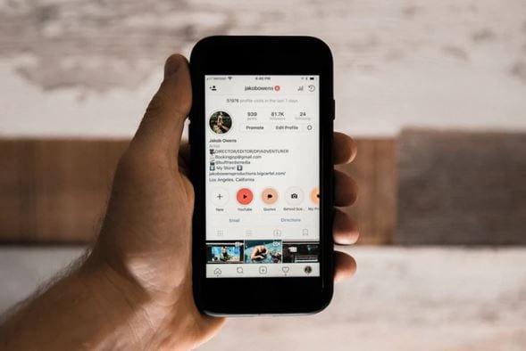 Ganhar seguidores no Instagram: imagem de uma mão segurando o celular com a tela do Instagram aberta