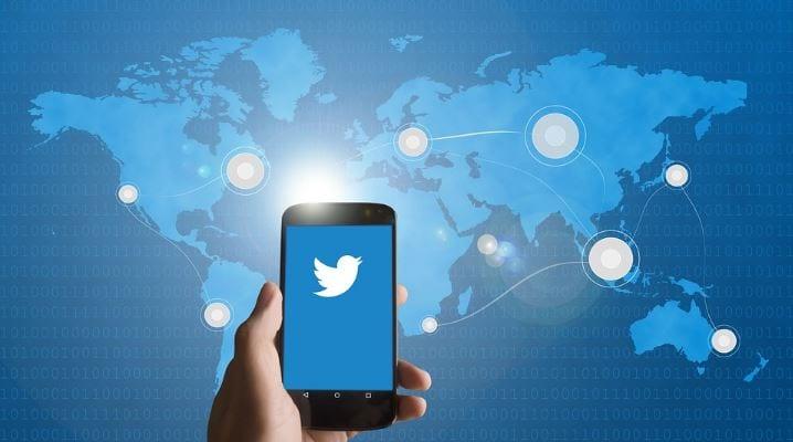 Twitter Trending Topics: imagem de uma mão segurando um celular com a logo do twitter na tela e a imagem de um mapa mundi no fundo em azul.