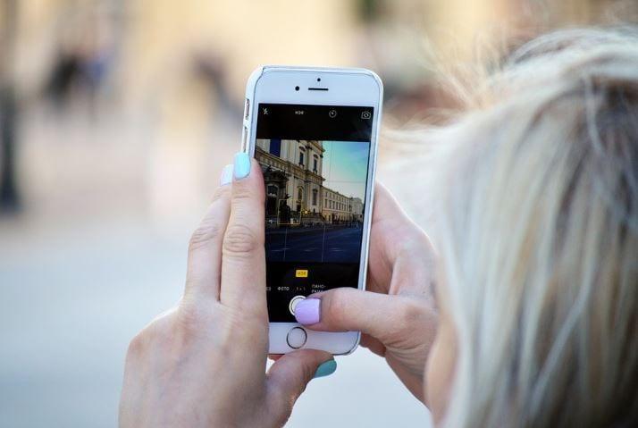 Stories Ads: imagem de uma mulher segurando um celular com a tela dos Stories aberta para gravar um vídeo