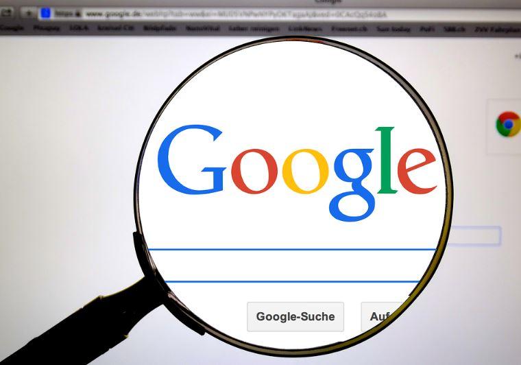 Etiqueta do Google Meu Negócio: imagem de uma lupa na frente da tela do computador com a página do Google aberta.