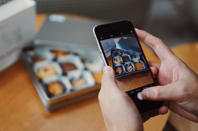 Fotos para Instagram: imagem de duas mãos segurando um celular tirando foto de uma caixa de doces em cima de uma mesa de madeira.