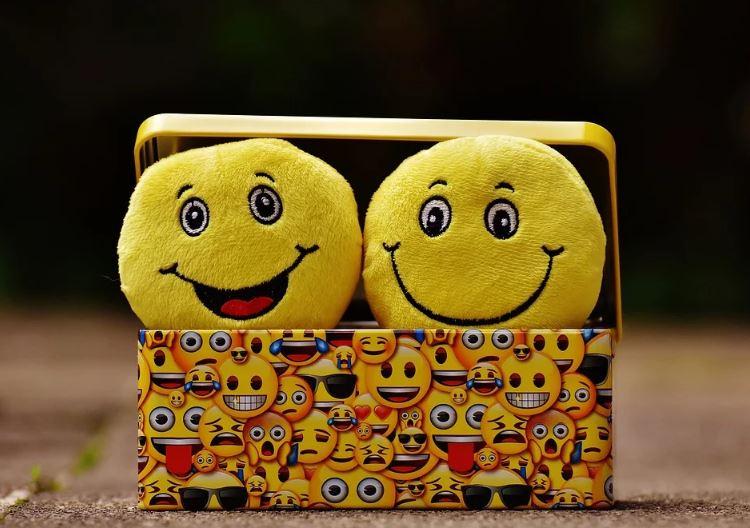 Emojis no marketing: imagem de dois emojis com sorriso apoiados em uma caixa estampada de emojis pequenos.