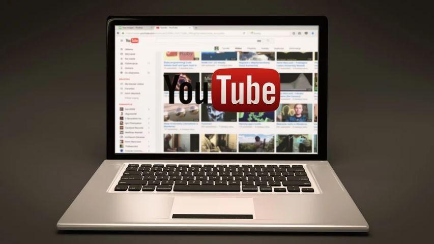 Youtube Analytics: Imagem de um notebook com a tela aberta no YouTube e o logo do Youtube na frente