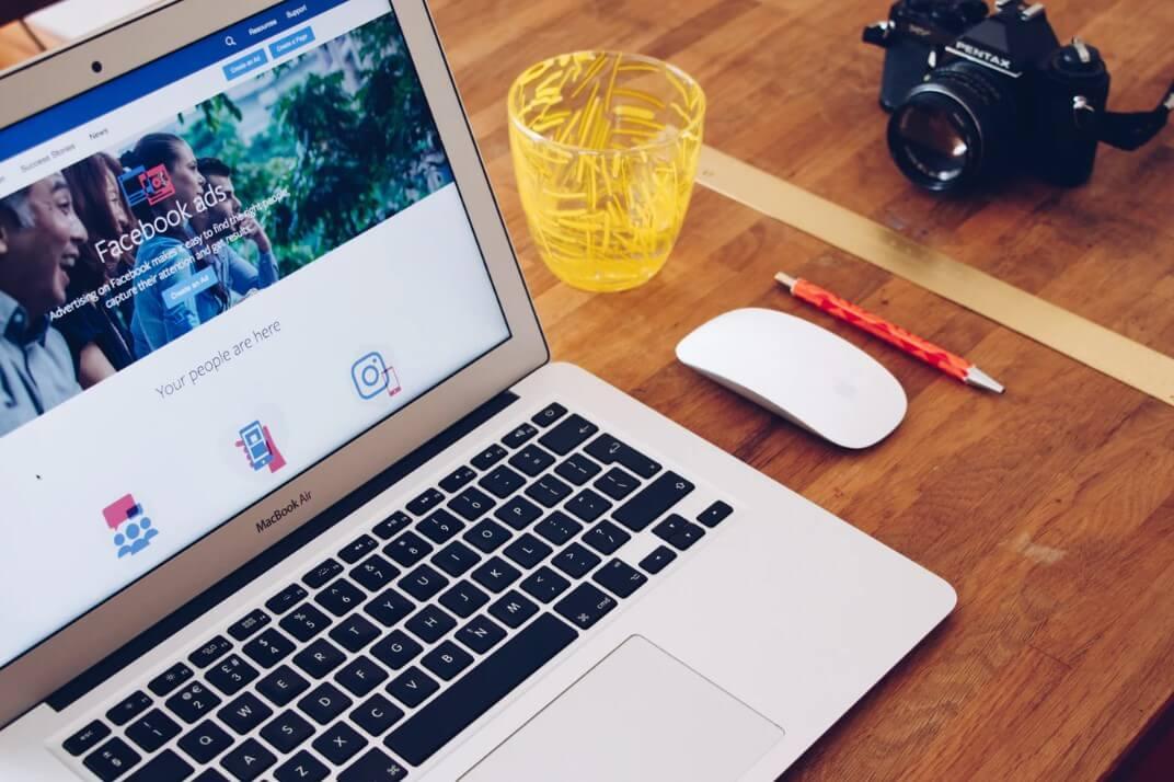 Criativo dinâmico do Facebook: imagem de um notebook em cima de uma mesa de madeira com a tela do Facebook Ads aberta.