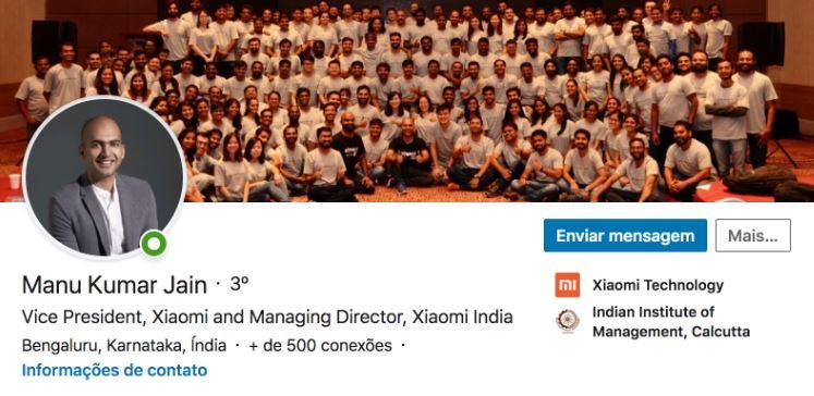 Perfil linkedin: imagem da capa e do perfil do Manu Kumar Jain, vice presidente da Xiaomi. no LinkedIn. A imagem da capa é de várias pessoas da empresa com a mesma camiseta posando para a foto.