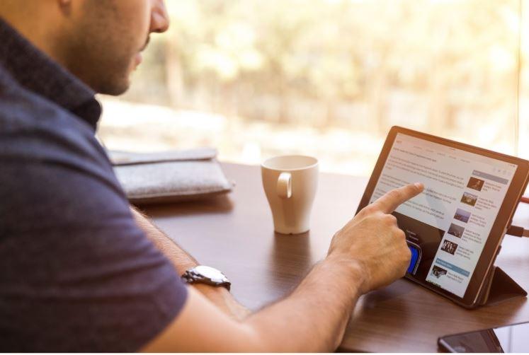 Perfil LinkedIn: imagem de um homem sentado apontando para a tela do tablet com a página do LinkedIn aberta. O tablet está sob uma mesa de madeira com uma caneca branca de cerâmica e um celular ao lado.