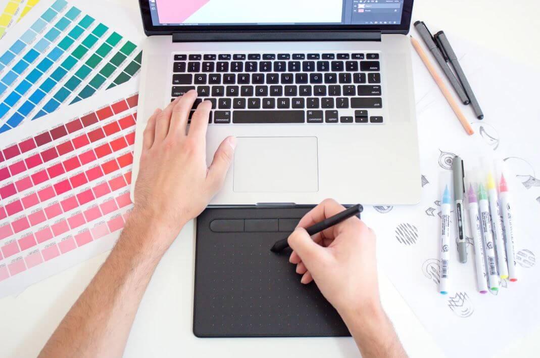 Social media design: imagem dois braços sob a mesa mexendo no notebook e no mouse com uma paleta de cores impressa do lado do notebook.