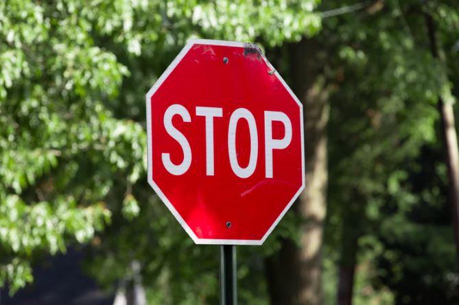 Social Media Design: imagem de uma placa de trânsito escrito Stop com o folhas de árvores ao fundo.