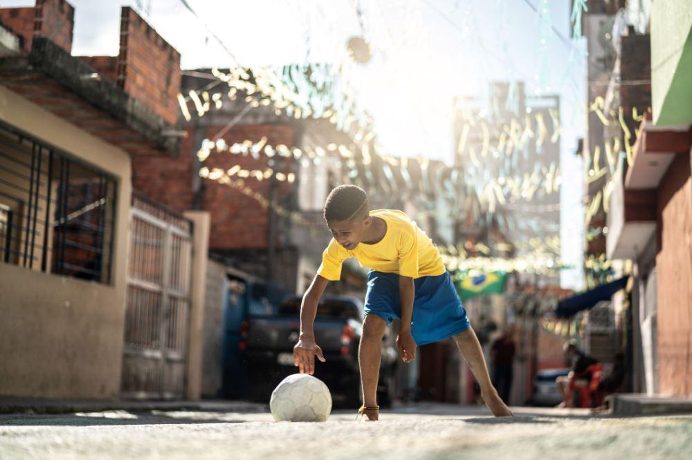 Dia das crianças nas redes sociais: imagem de um menino vestido de camiseta amarela e bermuda azul ajeitando uma bola no chão para brincar. A criança está na rua e algumas casas aparecem de fundo.