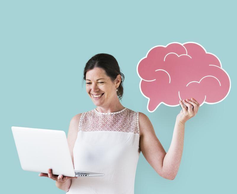 Como criar um logo: imagem de uma mulher segurando um notebook com uma mão olhando para a tela e segurando um cérebro desenhado na cor rosa na outra mão.