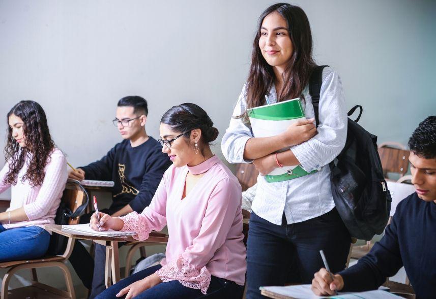 Como fidelizar alunos na escola: imagem de uma sala de aula com vários alunos sentados estudando e uma aluna em pé segurando o material