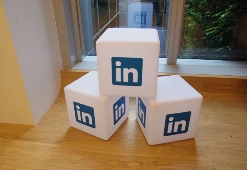 Linkedin Premium: imagem de três dados com a logo do linkedin impressa em cada, alinhados dois dados embaixo e um dado em cima, numa sala com piso de madeira