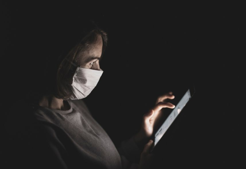 Comunicação em tempo de crise: imagem de uma mulher usando uma máscara branca no rosto mexendo no celular